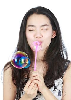 Jeune femme aisan soufflant des bulles