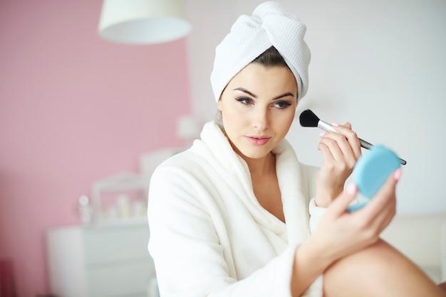 Jeune femme ajoutant du fard à joues sur ses joues