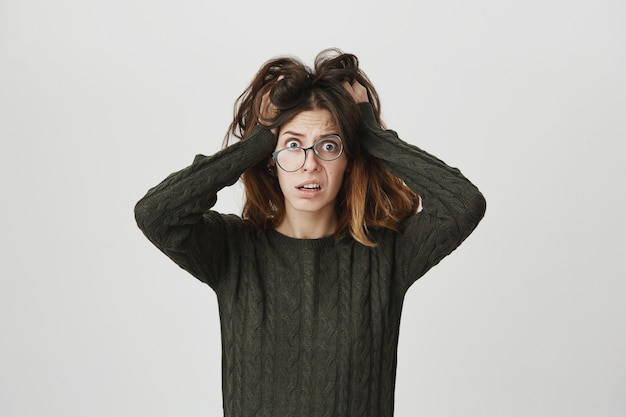 Jeune femme alarmée à lunettes, panique et ébouriffe les cheveux