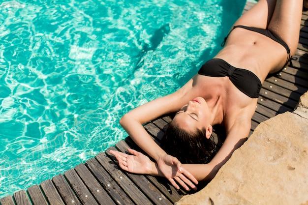 Jeune femme allongée au bord de la piscine