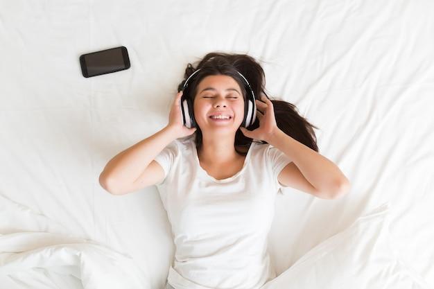 Jeune femme allongée sur un canapé et écoutant de la musique en se relaxant les yeux fermés