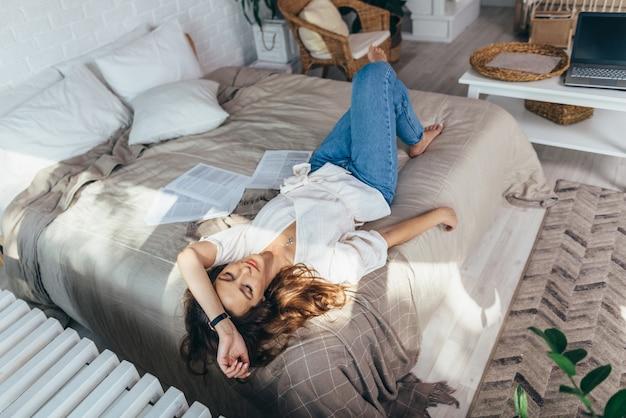 Jeune femme allongée sur le canapé avec les yeux fermés.