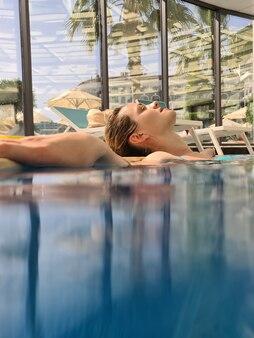 Jeune femme allongée sur le côté de la piscine avec les yeux fermés