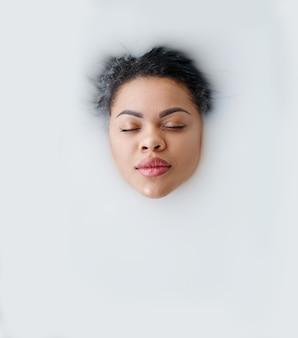 Jeune femme allongée dans le bain avec du lait, vue de dessus sur le visage. personne de sexe féminin dans la baignoire, soins de beauté et de santé au spa, traitement de bien-être dans la salle de bain