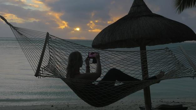 Jeune femme allongée dans un hamac sur la côte au coucher du soleil. elle prend des photos mobiles de l'océan et du selfie. bonnes vacances