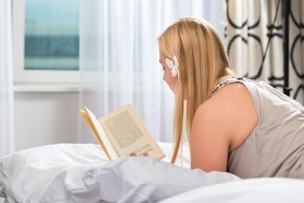 Jeune femme allongée dans le lit d'une chambre d'hôtel en lisant un livre,