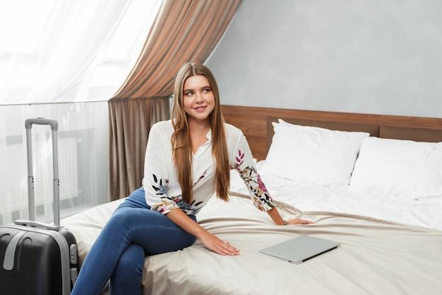 Jeune femme allongée dans le lit d'une chambre d'hôtel