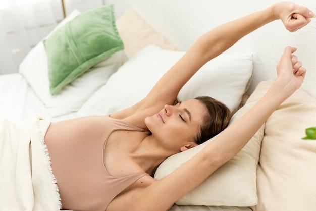 Jeune femme allongée dans son lit sous une couverture blanche, s'étirant, levant les bras et farniente dans sa chambre. bonjour.