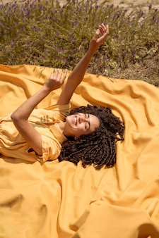 Jeune femme allongée sur un drap jaune dans la nature
