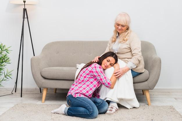 Jeune femme allongée sur les genoux de sa mère dans le salon