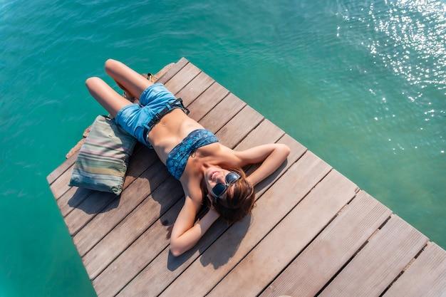 Une jeune femme allongée sur la passerelle en bois au bord de la mer sur l'isla de lobos, espace copier-coller, le long de la côte nord de l'île de fuerteventura, îles canaries. espagne