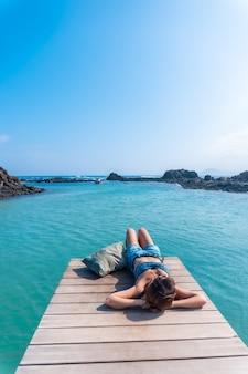 Une jeune femme allongée sur la passerelle en bois sur isla de lobos, au large de la côte nord de l'île de fuerteventura, îles canaries. espagne