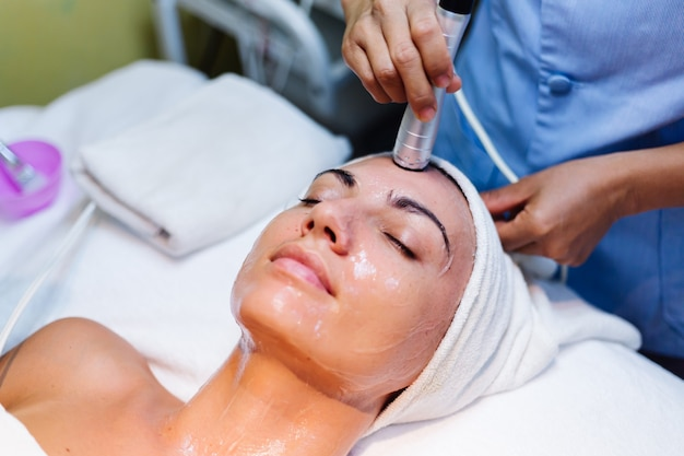 Jeune femme allongée sur la table du cosmétologue au cours de la procédure de rajeunissement