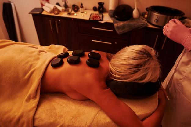 Jeune femme allongée sur une table de massage pendant une séance de massage aux pierres chaudes au spa