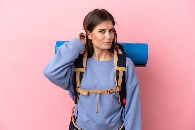 Jeune femme d'alpiniste avec un grand sac à dos d'isolement sur le fond rose ayant des doutes