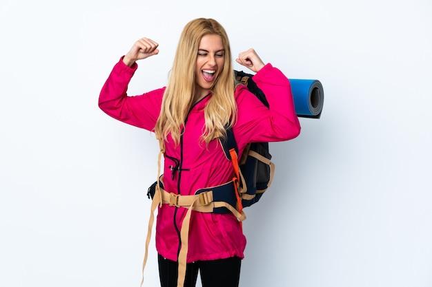 Jeune femme alpiniste avec un gros sac à dos sur blanc isolé célébrant une victoire