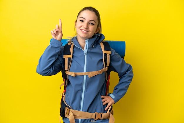 Jeune femme alpiniste avec un gros sac à dos sur fond jaune isolé pointant vers une excellente idée