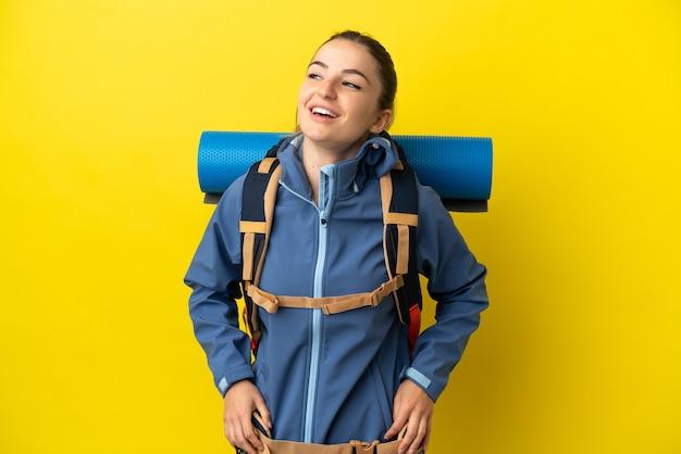 Jeune femme alpiniste avec un gros sac à dos sur fond jaune isolé posant avec les bras à la hanche et souriant