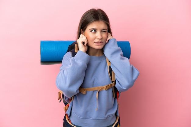 Jeune femme alpiniste avec un gros sac à dos isolé sur fond rose frustré et couvrant les oreilles