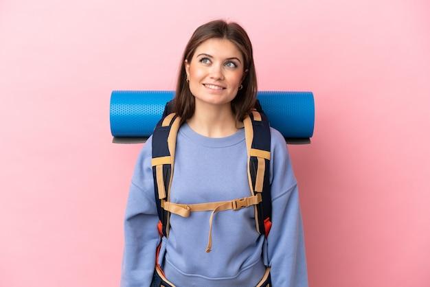 Jeune femme alpiniste avec un gros sac à dos isolé en pensant à une idée en levant les yeux