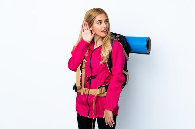Jeune femme alpiniste avec un gros sac à dos sur un mur blanc isolé écouter quelque chose