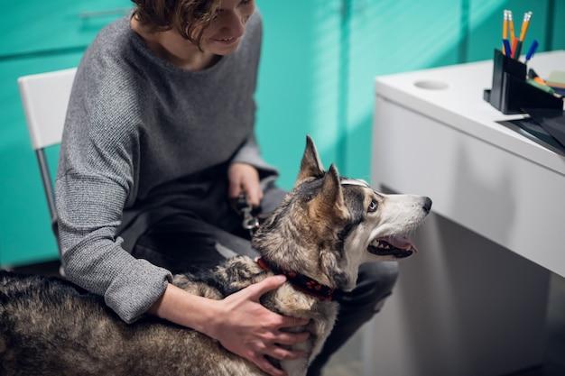 Une jeune femme amène son chien pour examen dans une clinique vétérinaire.