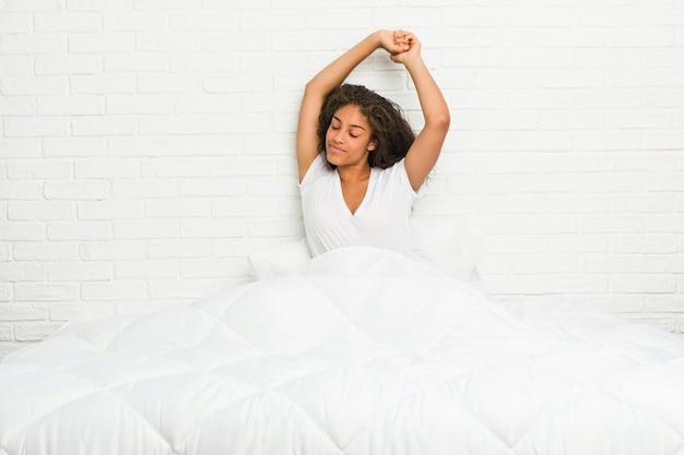 Jeune, femme américaine africaine, étirage, elle-même, lit