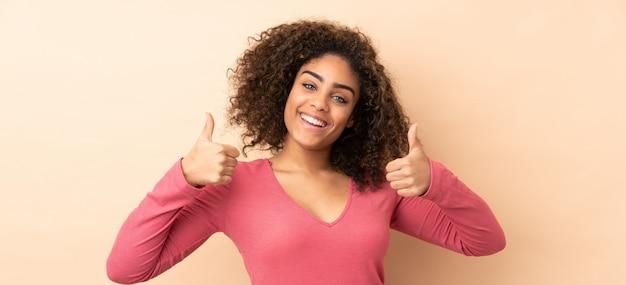 Jeune, femme américaine africaine, isolé, sur, espace beige, donner, a, pouce haut, geste