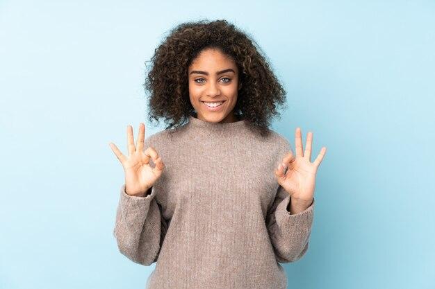 Jeune, femme américaine africaine, isolé, sur, espace bleu, projection, signe ok, à, deux mains