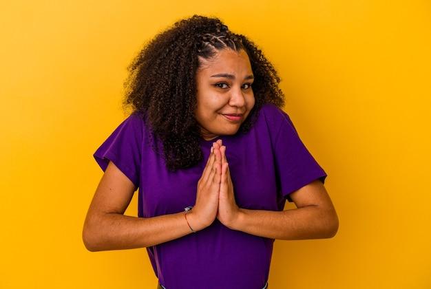 Jeune, femme américaine africaine, isolé, sur, mur jaune, tenant mains, dans, prier, près, bouche, se sent confiant