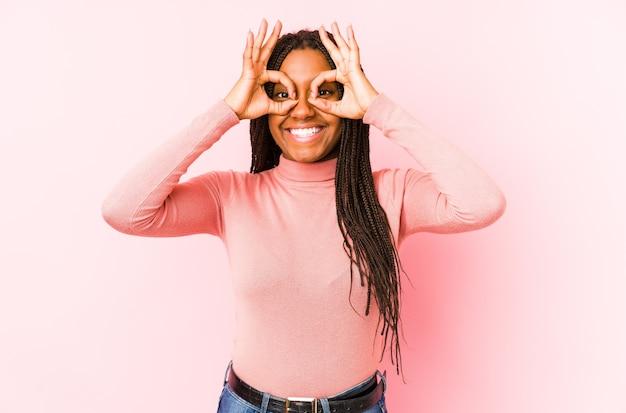 Jeune, femme américaine africaine, isolé, sur, rose, projection, ok, signe, sur, yeux