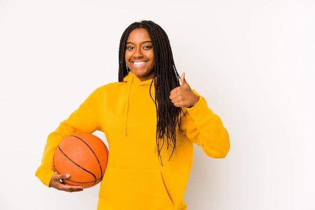 Jeune, femme américaine africaine, jouer basket-ball, isolé, sourire, et, lever pouce haut