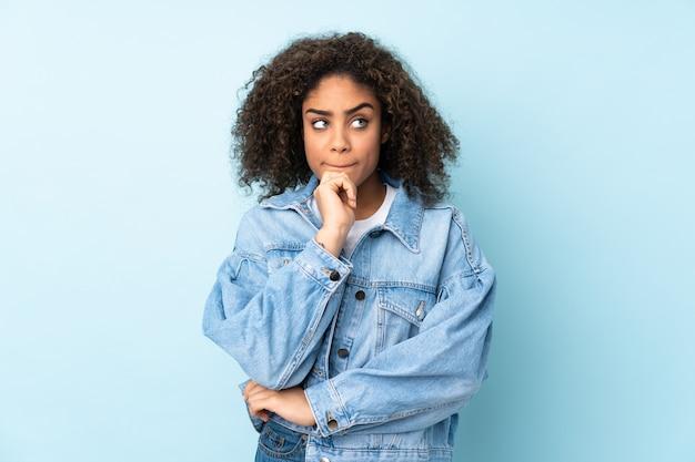 Jeune, femme américaine africaine, sur, mur bleu, avoir, doutes, et, pensée