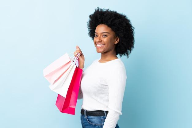Jeune, femme américaine africaine, sur, mur bleu, tenue, sacs provisions, et, sourire