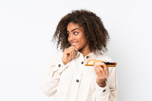 Jeune, femme américaine africaine, tenue, sushi, sur, mur blanc, penser, une, idée, et, regarder côté