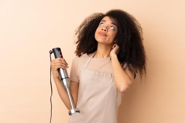 Jeune, femme américaine africaine, utilisation, mélangeur main, sur, mur beige, penser, une, idée
