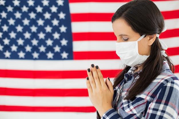 Jeune femme américaine avec le drapeau des usa en arrière-plan. porter un masque contre le coronavirus et prier.
