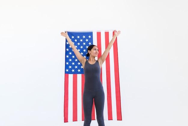Jeune femme américaine avec un drapeau usa dans ses mains sur une scène blanche. concept de la fête de l'indépendance du 4 juillet