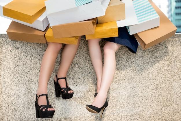 Jeune femme amis s'unissant ensemble tenant beaucoup de sacs à provisions
