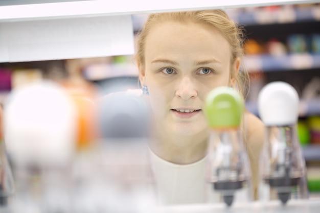 Jeune femme analysant des produits dans un magasin