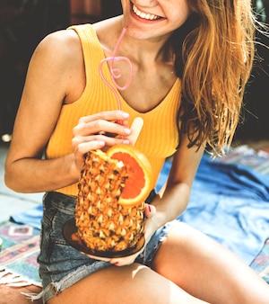 Jeune femme avec un ananas tropical
