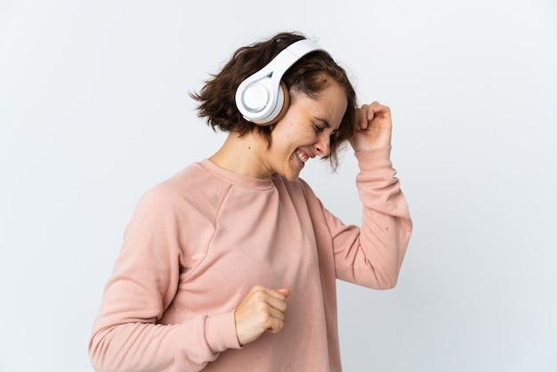 Jeune femme anglaise sur blanc écoute de la musique et de la danse