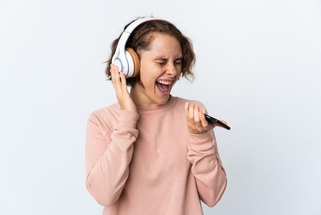 Jeune femme anglaise sur blanc écoute de la musique avec un mobile et le chant