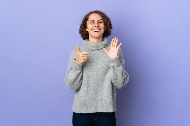 Jeune femme anglaise isolée sur fond violet comptant six avec les doigts