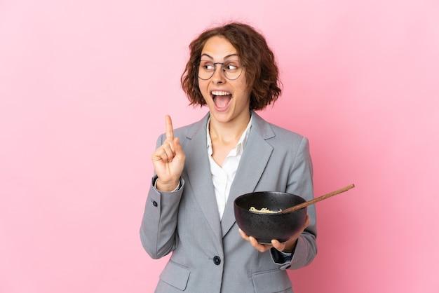 Jeune femme anglaise isolée sur un mur rose dans l'intention de réaliser la solution tout en soulevant un doigt tout en tenant un bol de nouilles avec des baguettes