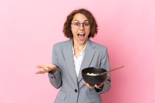 Jeune femme anglaise isolée sur un mur rose avec une expression faciale choquée tout en tenant un bol de nouilles avec des baguettes