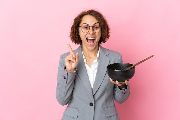 Jeune femme anglaise isolée sur un mur rose pointant vers le haut une excellente idée tout en tenant un bol de nouilles avec des baguettes