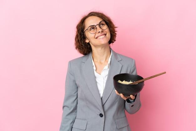 Jeune femme anglaise isolée sur un mur rose à la recherche en souriant tout en tenant un bol de nouilles avec des baguettes