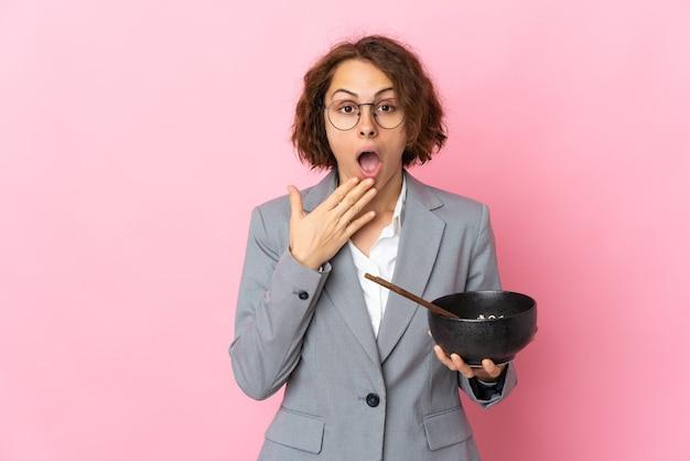 Jeune femme anglaise isolée sur un mur rose tenant un bol de nouilles avec des baguettes et surpris