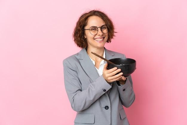 Jeune femme anglaise isolée sur un mur rose tenant un bol de nouilles avec des baguettes
